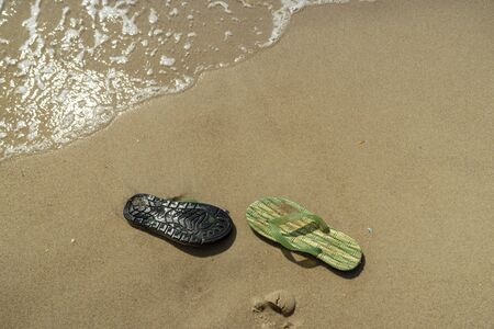 pair, two of men's beach slippers on the sand on the beach by the sea or ocean