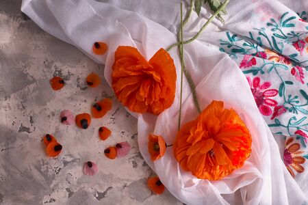 Stillife with red poppies on grey concrete background and white drappery.