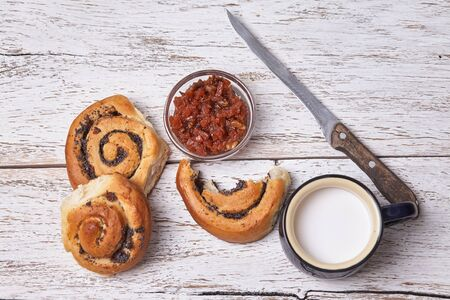 Variety of homemade puff pastry buns cinnamon served with milk cup, jam, butter as breakfast over white plank wooden background. Flat lay, space Standard-Bild