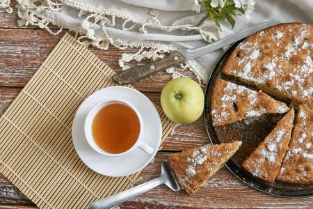 Homemade pie with cherries and apples white cup of tea on a dark rustic wooden board background. Rustic style food Banco de Imagens