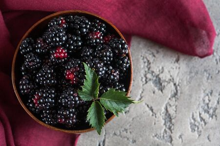 Sweet blackberry and leaves in wooden bowl on grey stone background. Top view. Standard-Bild
