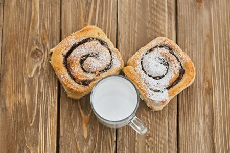 Basket of homemade buns with jam, served on old wooden table with cup of milk Standard-Bild