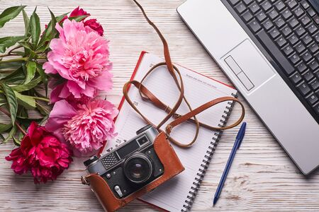 Flat lay women's office desk. Female workspace with laptop, pink peonies bouquet, camera and coffee on white background. Top view feminine background.