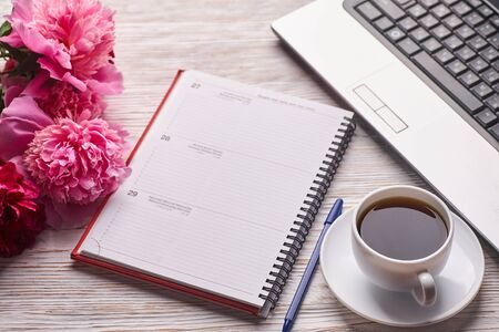 Flat lay women's office desk. Female workspace with laptop, pink peonies bouquet and coffee on white background. Top view feminine background. Standard-Bild