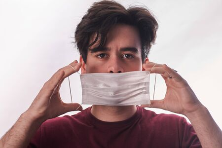 Young man hands putting new respirator mask for mouth and nose covering in virus quarantine time. First protection. Healthcare concept. Closeup. Front view. Standard-Bild - 150239594