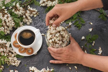 Spring layout with Coffee on table and white acacia flowers. Female hands pour acacia flowers into a cup Standard-Bild