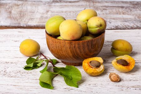 ripe organic apricots fruits in ash tree wooden bowl on a white wooden background Standard-Bild - 150239569