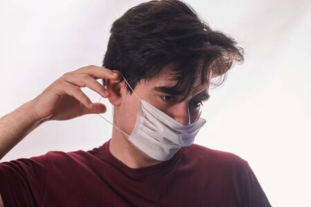 Young man hands putting new respirator mask for mouth and nose covering in virus quarantine time. First protection. Healthcare concept. Closeup. Front view. Standard-Bild - 150239571