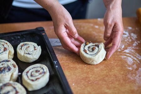 Preparation of cinnamon rolls. A woman puts buns of buns on a baking tray. Standard-Bild
