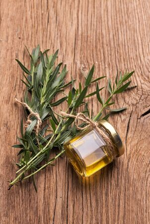 Top view Bottle glass of essential rosemary oil with rosemary branch on wooden rustic background. Standard-Bild - 150457619