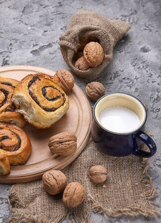 Basket of homemade buns with jam, served on old wooden table with walnuts and cup of milk Standard-Bild - 150515787