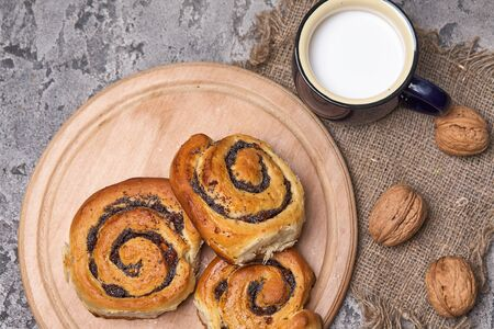 Basket of homemade buns with jam, served on old wooden table with walnuts and cup of milk Standard-Bild - 150453466
