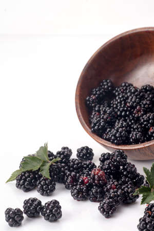 Blackberries in a wooden bow. Ripe and tasty black berry isolated on white. Blackberries on a white background.