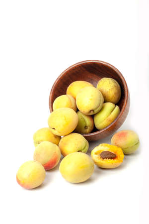 Fresh ripe apricots in wooden bowl isolated on a white background. Standard-Bild - 150677086