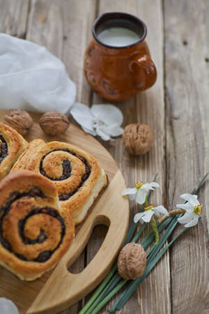 Basket of homemade buns with jam, served on old wooden table with walnuts and cup of milk Standard-Bild - 150900404