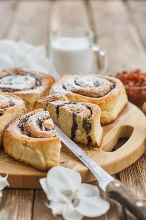 Basket of homemade buns with jam, served on old wooden table with walnuts and cup of milk Standard-Bild - 150900420
