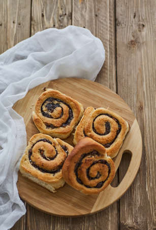Tasty buns with raisins on a brown rustic wooden table. fresh bakery. breakfast. bread. top view Standard-Bild - 150900895