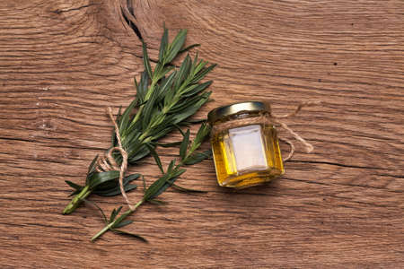 Top view Bottle glass of essential rosemary oil with rosemary branch on wooden rustic background. Standard-Bild