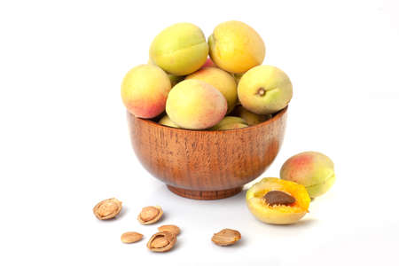 Fresh ripe apricots in wooden bowl isolated on a white background. Standard-Bild - 151039096