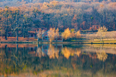 Colorful autumn forest with reflection in water of calm lake. Standard-Bild - 151077021