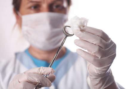 theater assistant preparing swab for surgeon
