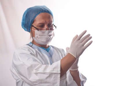 Protecting healthcare workers from infection. A female doctor puts on medical gloves on a white isolated background and smiles. Personal protective equipment before examination of patients
