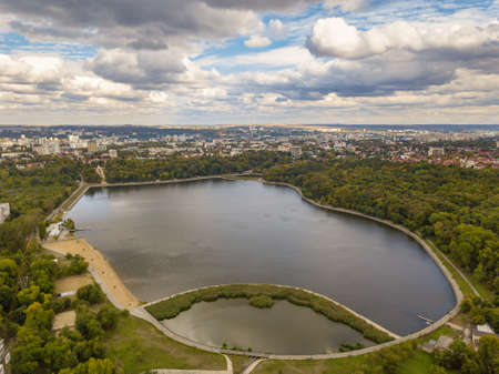 Aerial view of a lake in a park with autumn trees. Kishinev, Moldova. Epic aerial flight over water. Colorful autumn trees in the daytime.