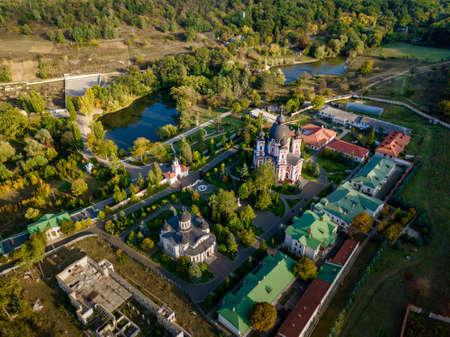 Flight over a christian monastery surrounded by autumn forest. Kurky monastery, Moldova republic of.