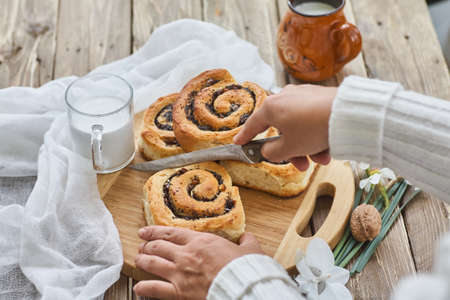 Female hand cuthomemade buns with jam, served on old wooden table with walnuts and cup of milk Standard-Bild