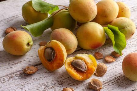 Apricot fruit. Fresh organic apricots on a white wooden background. Vega food.