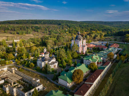 Flight over a christian monastery surrounded by autumn forest. Kurky monastery, Moldova republic of. Foto de archivo