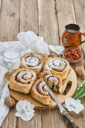 Basket of homemade buns with jam, served on old wooden table with walnuts and cup of milk