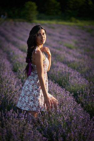Portrait of lovely brunette girl in lavender field. Summer lavender model posing in front of the camera.