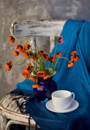 A Little Red Poppies Bouquet in blue vase on vintage chair. Poppies and cup of coffee. Фото со стока