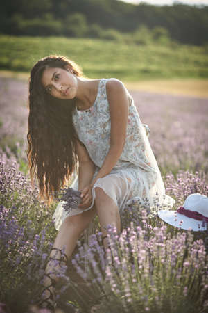Beautiful girl in a white sarafan sits on a wooden chair and poses in the middle of a lavender field.