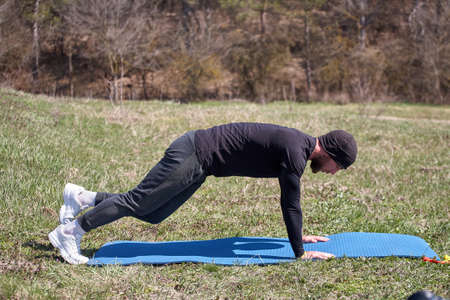 Playful sportsman extends leg behind him on fitness mat in the park