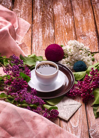 Coffee Cup And Colorful Lilac Flowers On Garden wooden Table