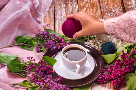 Hand holds a cup of morning coffee with spring lilac flowers branches blossoming on wooden background view from above. Flat lay underground style. Expensive colors. Creative design of flowers. Standard-Bild