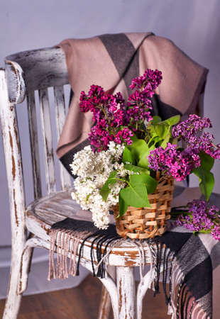 Lillac bouquet in vase on Vintage wooden chair