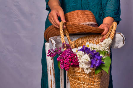 Woman holding hands wicker bag with lilac flowers indoor