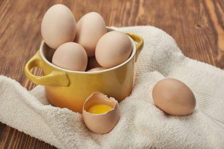 Bowl of raw chicken eggs on the wooden background Standard-Bild