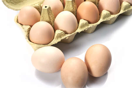 Close-up of eggs in cartoon on white background. Raw chicken eggs in egg box organic food for good health high protein.