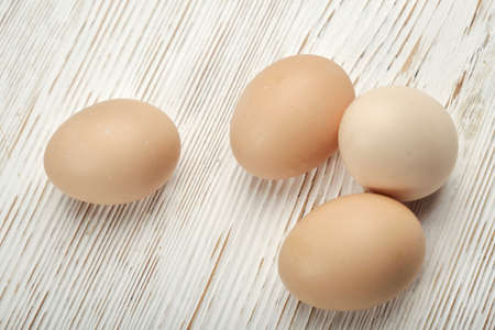 Close-up view of raw chicken eggs on wooden background. Raw chicken eggs in egg box organic food for good health high protein. Standard-Bild