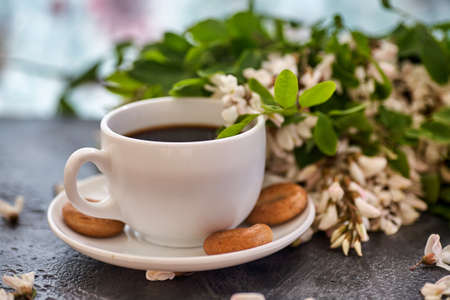 Cup of coffeel and acacia closeup. Nutrition. background with a cup of Coffee and acacia flowers.