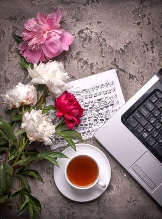 Coffe, peonies and laptop on gray vintage background