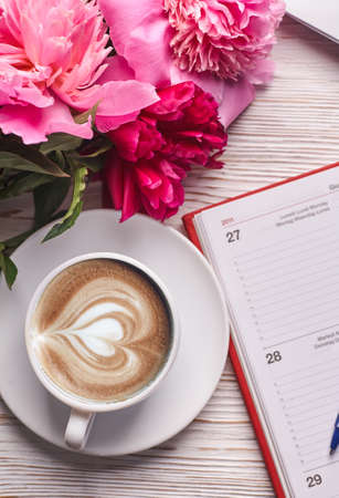 Morning coffee mug for breakfast, empty notebook, pencil and pink peony flowers