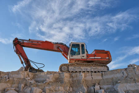 Excavator stands on the bacExcavator stands on the background of a stone quarry.kground of a stone quarry. Standard-Bild