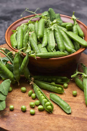 Pods of green peas with leaves in bowl on wooden table