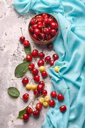 Ripe red and yellow cherries in bowl on gray background