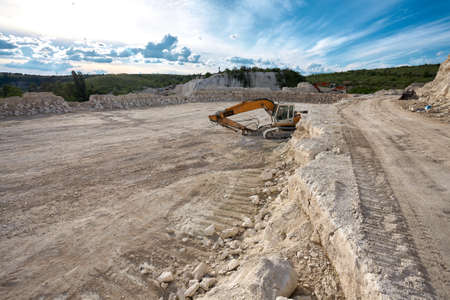 Excavator stands on the background of a stone quarry.